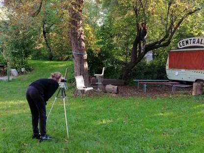 Eine Frau fotografiert mit einer Kamera auf einem Stativ einen umgebauten Wohnwagen neben Bäumen im Sonnenpark. (Foto: Lia Quirina)
