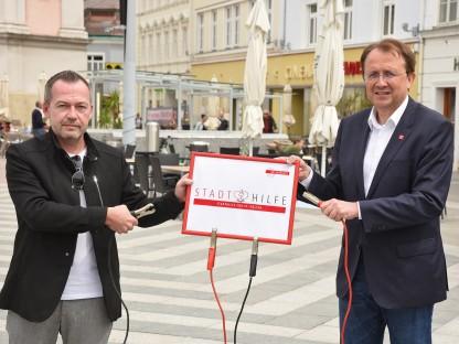 Bürgermeister Matthias Stadler und Michael Bachel vom Wirtschaftsservice mit Schild am Rathausplatz. (Foto: Vorlaufer)