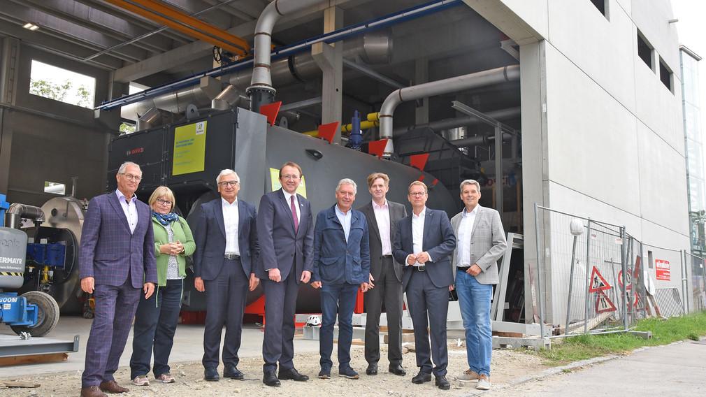 Geschäftsführer und ProkuristInnen der Fernwärme, EVN Vorstandsmitglieder und der Vizepräsident der EVN bei einem Gruppenfoto. Im Hintergrund sieht man die neue Anlage des FHK Nord in St. Pölten