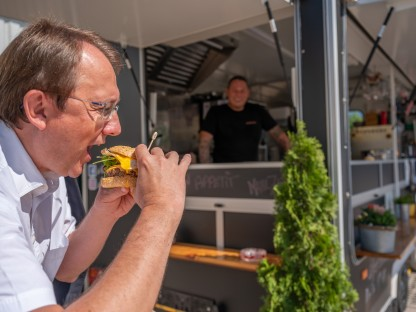 Bürgermeister Matthias Stadler beim Abbeißen von einem Burger, im Hintergrund sind der Foodtruck s'Hutsch und Thomas Haiderer zu sehen. (Foto: Arman Kalteis)