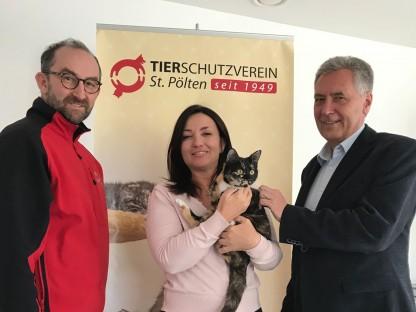 Zwei Männer mit Frau und Katze vor Tierschutzverein Plakat.(Foto: Bernhard Stiowicek).