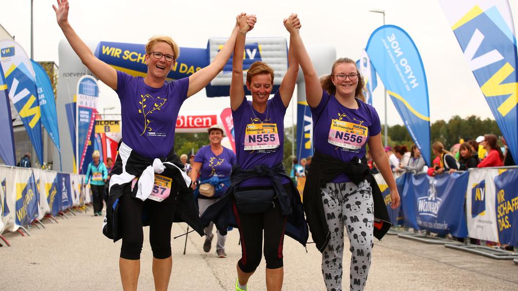 Im Vordergrund sind drei Frauen Hand in Hand zu sehen, die ihre Arme jubelnd in die Höhe strecken. Im Hintergrund sind Zuschauer und Zuschauerinnen sowie weitere Läuferinnen zu sehen. (Foto: Peter Schneider)