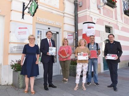 Eine Abordnung aus dem Rathaus präsentiert den neuen Tagungsfolder vorm Tourismusbüro. (Foto: Vorlaufer)
