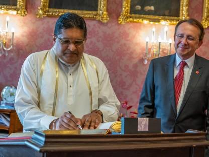Der Sri  Lankische Botschafter steht im Bürgermeisteerzimmer. vor einem Stehpult und trägt sich in das Goldene Buch ein. Rechts hinter ihm im Bild, ist Bürgermeister Matthias Stadler zu sehen.