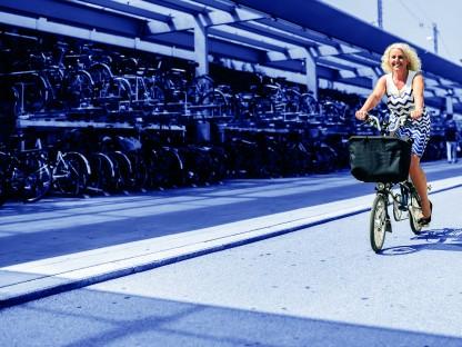 Frau auf einem Fahrrad vor einer Fahrradgarage am St. Pöltner Hauptbahnhof. (Foto: Robert Alexander Herbst)