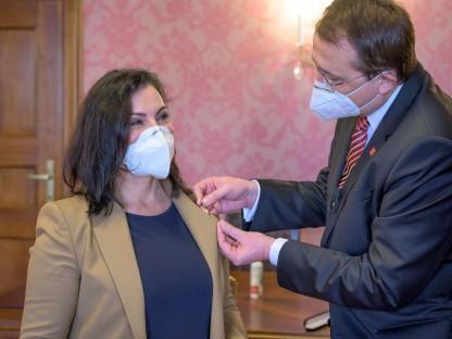 Bürgermeister Matthias Stadler steckt die Nadel mit dem Ehrenzeichen der Stadt St. Pölten an das Jackett von Prim. Dr. Sonja Gobara an.