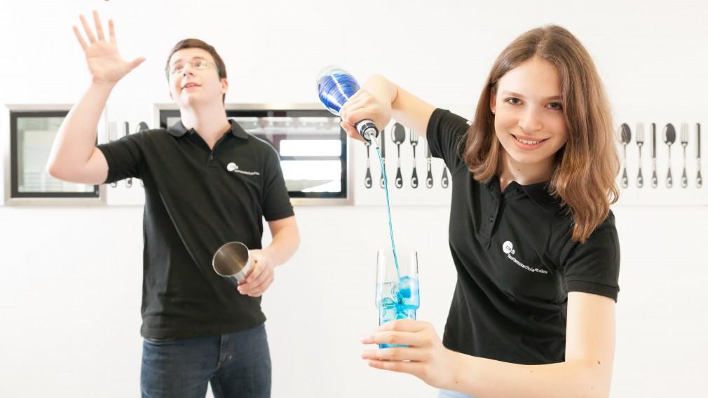 Eine Schülerin beim Einschenken und ein Schüler beim Jonglieren mit Cocktailmixbecher. (Foto: Fotoprofis/Gerald Lechner).