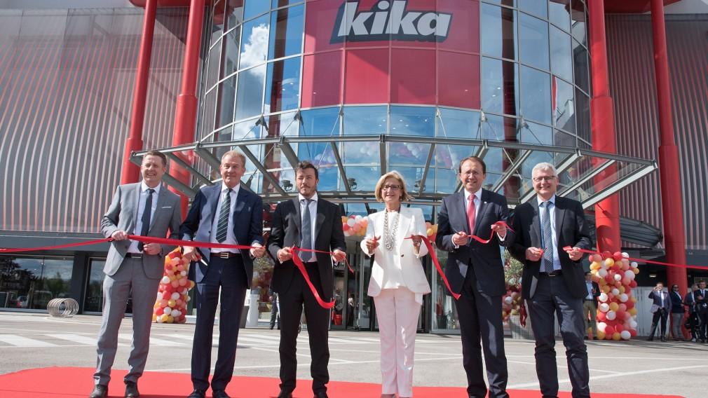 Mehrere Personen stehen für ein Gruppenfoto vor der neuen Kika-Filiale.