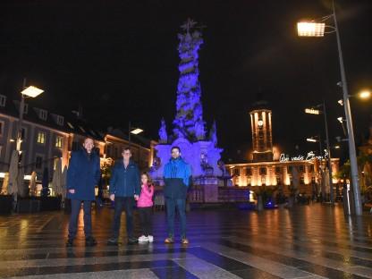 Der Bürgermeister von St. Pölkten und Mitarbeiter der Straßenbeleuchtung stehen vor der Pestsäule am Rathausplatz.