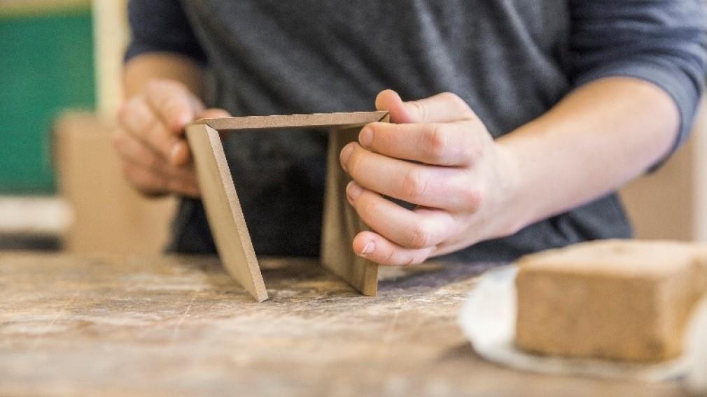 Blick auf zwei Hände beim Werken mit kleinen Holzplatten. (Foto: Severin Wurnig).