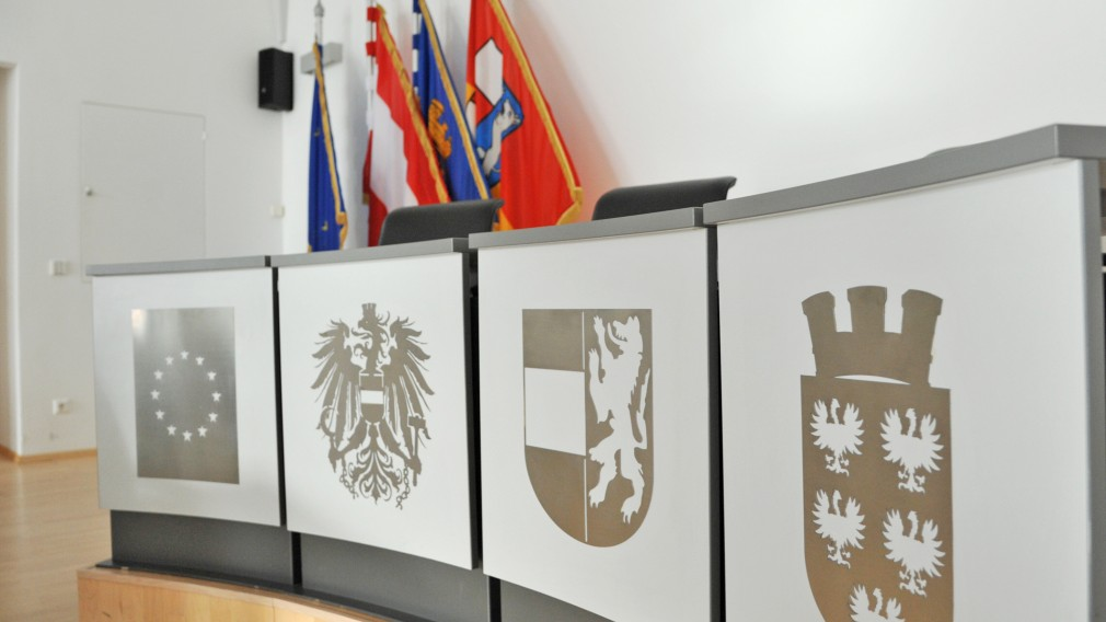 Blick in leeren Sitzungssaal im Rathaus auf Rednerpult und Fahnen. (Foto: Josef Vorlaufer)