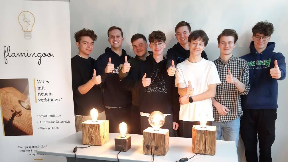 Werbeplakat daneben Tisch mit Tischlampen aus Holz mit Glühbirnen gefertigt dahinter stehen HTL Schüler (Foto: HTL St. Pölten