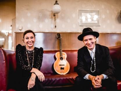 Ursula Strauss und Ernst Molden sitzend auf einer Couch. Im Hintergrund sieht man eine Gitarre. (Foto: Daniela Matejschek)