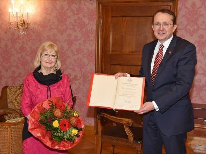 Bürgermeister Matthias Stadler hält Urkunde, Eva Riebler-Übleis hält einen Blumenstrauß. Beide stehend im Bürgermeisterzimmer. (Foto: Josef Vorlaufer)