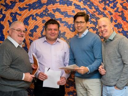 Dr. Josef Wildburger, Mag. Jürgen Erber, DI Paul Pfoser und Mag, Philip Simson stehend vor Wandbild. (Foto: Tanja Wagner)