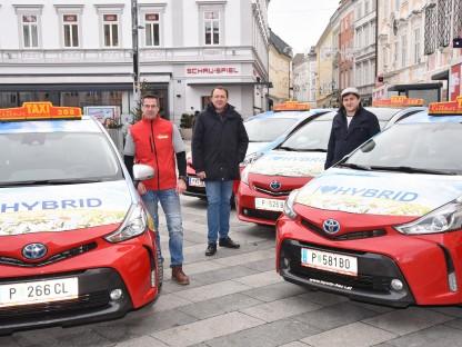 Taxifahrer Roman Habersam, Bürgermeister Matthias Stadler und Jugendgemeinderat Gregor Unfried stehend zwischen Taxis am Rathausplatz. (Foto: Josef Vorlaufer)
