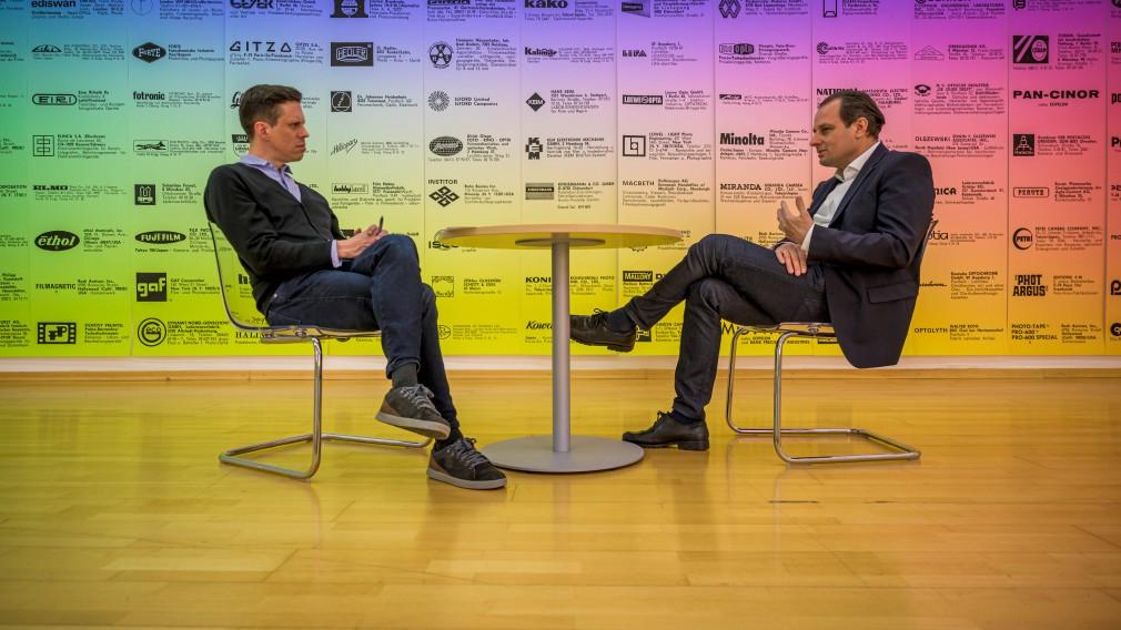Michael Koppensteiner im Gespräch mit Alfred Kellner, sitzend, dazwischen ein runder Tisch, im Hintergrund eine farbig gestaltete Plakatwand. (Foto: Arman Kalteis)
