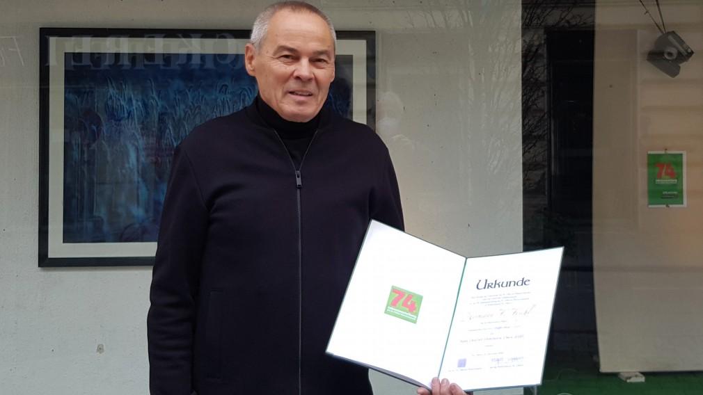 Hermann F. Fischl mit Urkunde vor seinem Atelier. (Foto: Kienzl,2020)