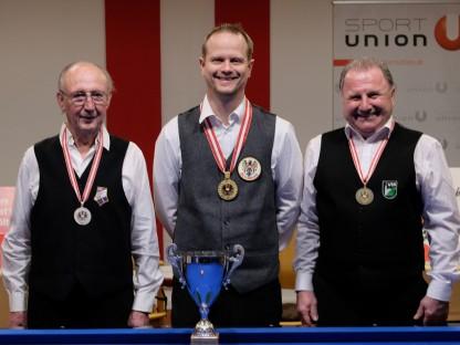Drei Männer mit Medaille und Pokal vor Billardtisch