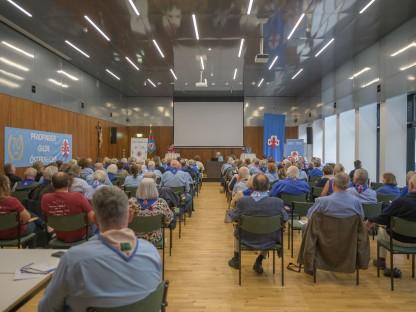 Viele Personen sittzen in einem Veranstaltungsraum und ören einem Redner zu.