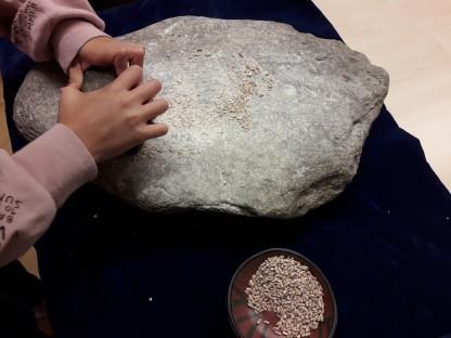 Kinderhände mit Stein und Schüssel mit Getreide. (Foto: Stadtmuseum).