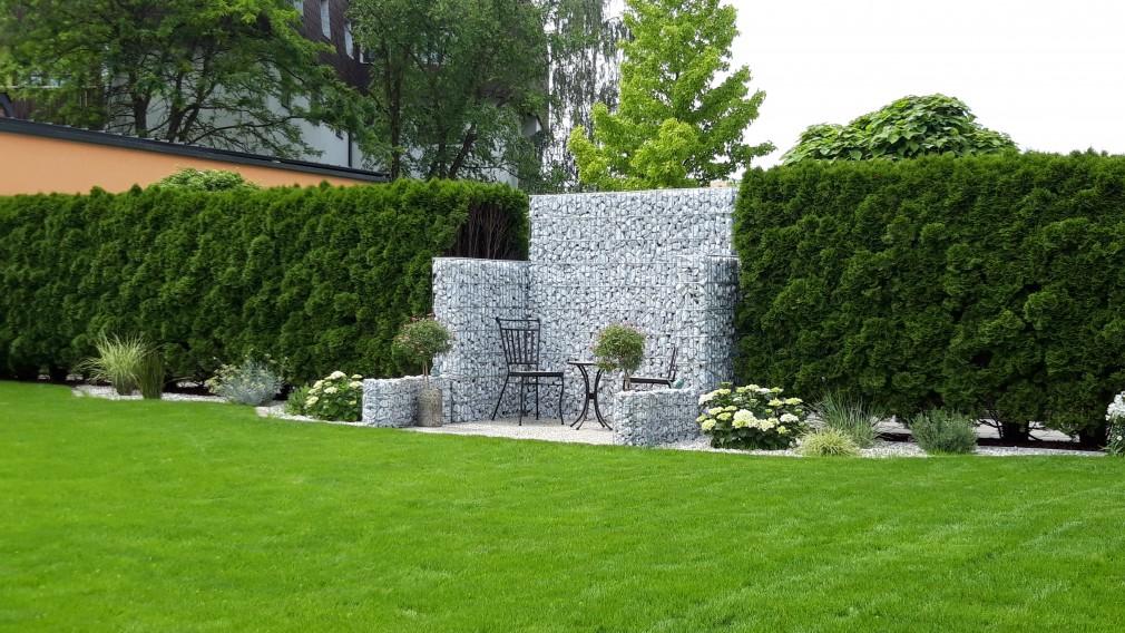 Blick auf Rasen in einen Garten im Hintergrund, eine Hecke, Sträucher und  Platz mit Steinmauer kleinen Tisch und zwei Sesseln. (Foto: Andrea Heinzl)