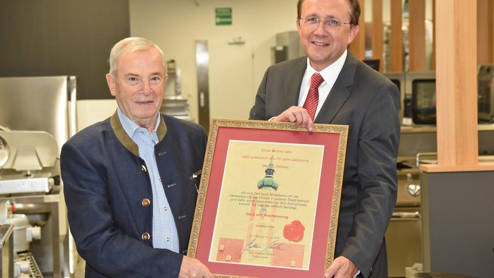 Ernst Stölner und Bürgermeister Matthias Stadler stehen nebeneinander und halten dabei eine Urkunde in der Hand.