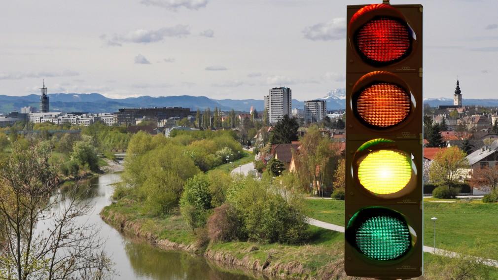 Im Vordergrund eine vierstufige Ampel, im Hintergrund ein Blick auf die Stadt. Die Ampel leuchtet gelb (Fotomontage Josef Vorlaufer).