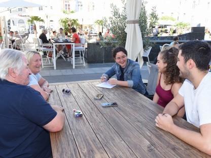 Zwei Männer und drei Frauen sitzen bei einem Tisch im Freien am Rathausplatz. (Foto: Josef Vorlaufer).