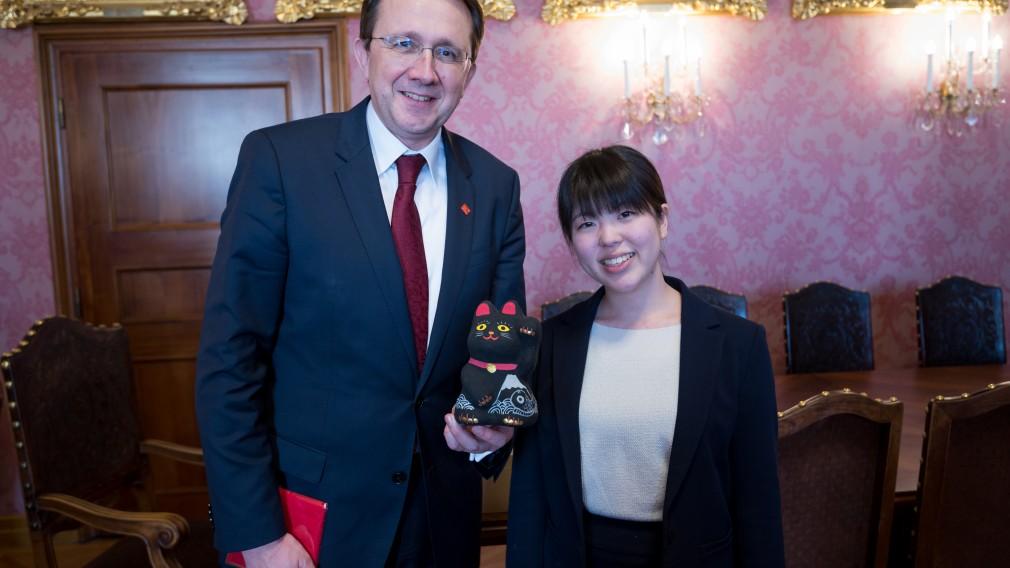 Bürgermeister Mag. Mathias Stadler hält eine Manekineko in der Hand, dabei handelt es sich um einen beliebten japanischen Glücksbringer in Gestalt einer aufrecht sitzenden und mit der Hand winkenden Katze. Neben dem Bürgermeister steht die japanische Austauschschülerin Airi Inque, die dem Bürgermeister die Katzenfigur geschenkt hat.