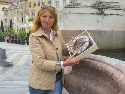 Themenbegleiterin Anita Schuster mit einer Prandtauertorte am Rathausplatz. (Foto: A. Behpournia)