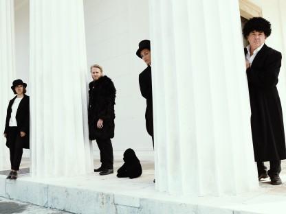 Schauspielerinnen und Schauspieler stehend bei weißen Säulen. (Foto: Alexi Pelekanos.)