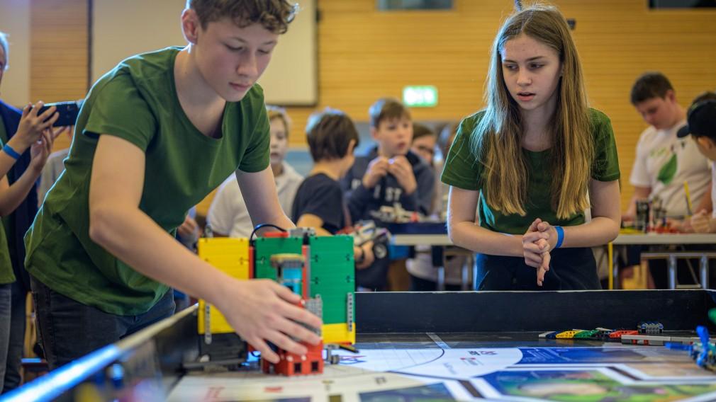 Zwei Mitglieder eines Teams vom BRG/BORG St. Pölten bedienen während des Wettbewerbs ihren Roboter.