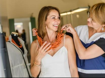 Katrin Surin legt in ihrem Schmuckgeschäft Dali Reisinger eine wunderschöne, orangerote Korallenkette um den Hals.