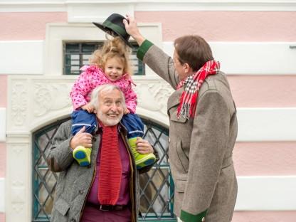 Ein Mädchen sitzt auf den Schultern eines älteren Herren. Der Bürgermeister Matthias Stadler steht nebenbei uns setzt dem Mädchen einen Hut auf. (Foto: Tanja Wagner)