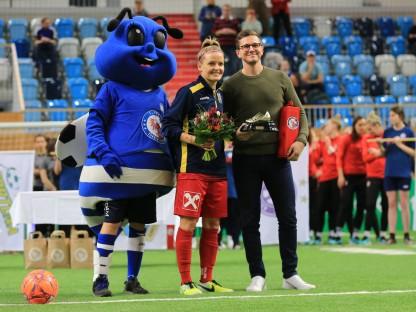 SKN Spielerin Isabelle Meyer bei Blumenübergabe mit Fußball Maskotchen auf Spielfeld