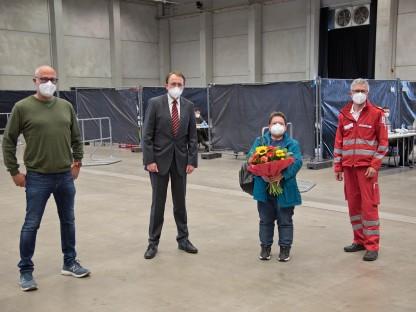 Der Sicherheitsbeauftragte der Stadt St. Pölten Peter Puchner, Bürgermeister Matthias Stadler, Monika Hofbauer, bei der die hunderttausenste Testung durchgeführt wurde und der Bezirksstellenleiter des Roten Kreuzes Werner Schlögl stehen in der Testhalle im VAZ St. Pölten nebeneinander.