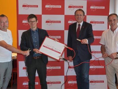 Vier Personen mit Schild und Starterkabel. (Foto: Mayer)