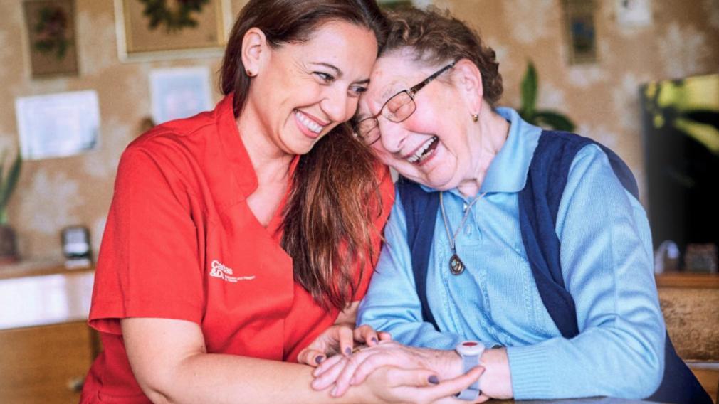 Eine Caritas-Mitarbeiterin sitzt Hand-in-Hand mit einer Seniorin an einem Tisch. Beide lachen und sind sichtlich über die Anwesenheit des Gegenübers sehr erfreut.