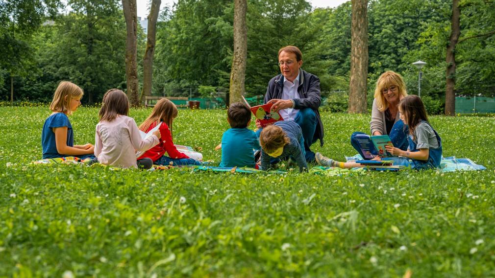 Kindern wird im Park vorgelesen von zwei Erwachsenen. (Foto: Arman Behpournia)