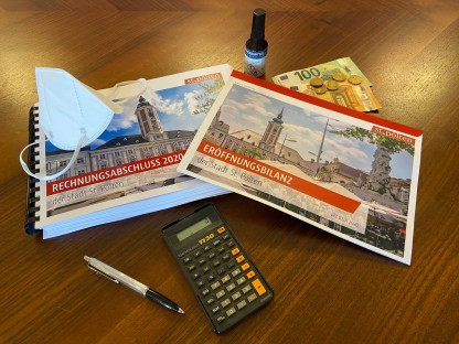 Die Broschüren zum Rechnungsabschluss, ein Taschenrechner, Geldscheine und Münzen, eine Schutzmaske und ein Fläschchen Desinfektionsmittel auf einem Tisch. (Foto: Josef Vorlaufer)