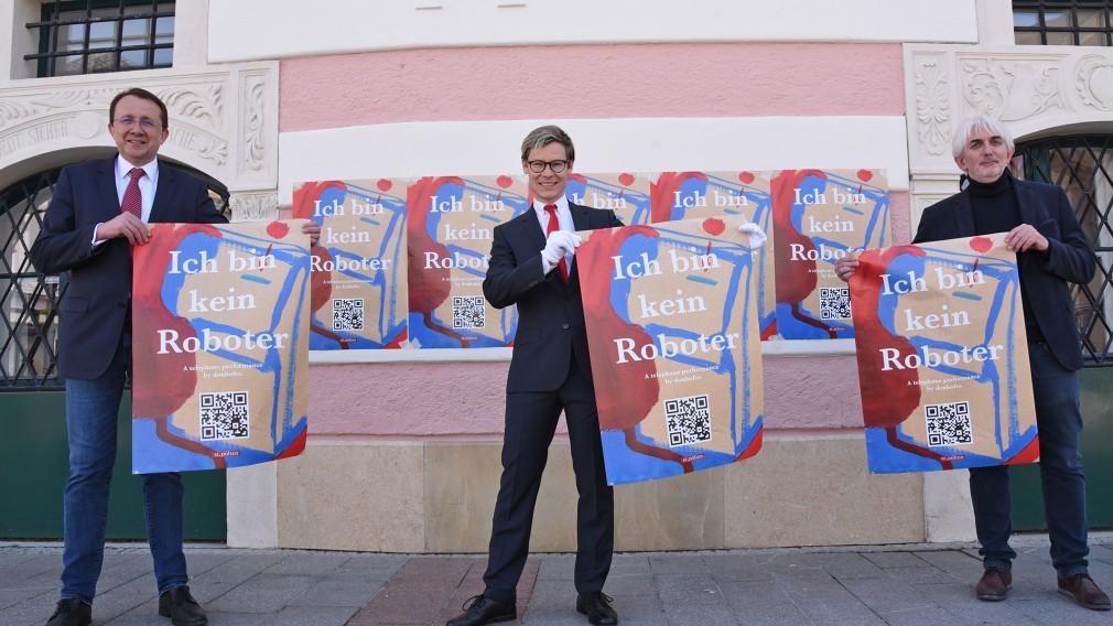 """""""Wir sind keine Roboter. Wir sind Menschen"""": Aktionskünstler donhofer., Bürgermeister Matthias Stadler und Museumsleiter Thomas Pulle präsentieren die neue Kunstaktion. (Foto Josef Vorlaufer)"""