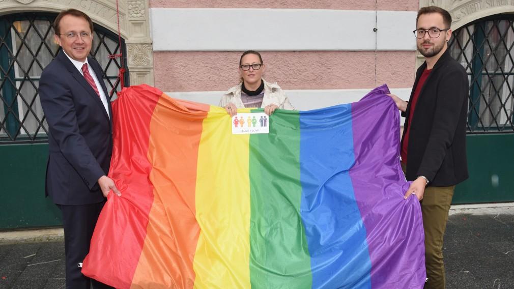 Zwei Männer und eine Frau halten eine Regenbogenfahne vor dem Rathaus. (Foto: Josef Vorlaufer)
