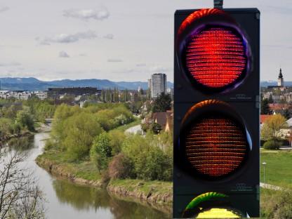 Im Vordergrund eine vierstufige Ampel, im Hintergrund ein Blick auf die Stadt. Die Ampel leuchtet rot. (Fotomontage: Josef Vorlaufer)