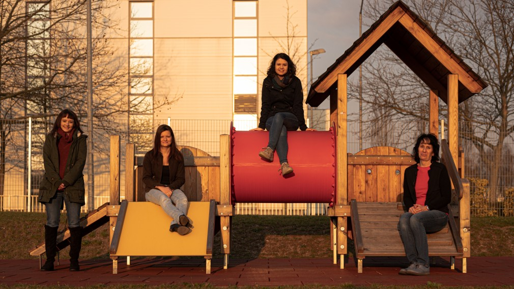 Vier Kindergartenpädagoginnen, sitzen verteilt auf einem Klettergerüst auf dem Spielplatz des Kindergartens in der  Karl Pfeffer-Gasse.