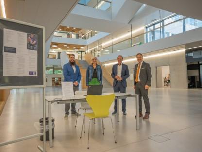 Vier Personen befinden sich im neuen Gebäude der Fachhochschule St. Pölten und lachen für ein Gruppenfoto in die Kamera.