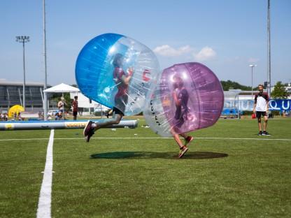 zwei Jugendliche hüpfen geschützt durch einen aufgeblasenen Ganzkörperball aufeinander zu (Foto: Andreas Simon)