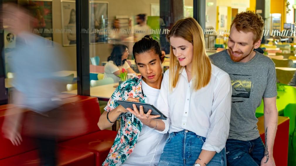Studenten und Studentin schauen auf I-Pad.(Foto: Martin Lifka Photography)