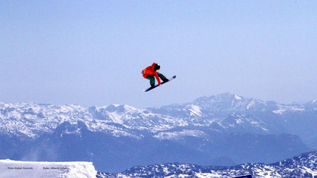 Snowboarder Julian Maschl beim Sprung mit verschneiter Berglandschaft