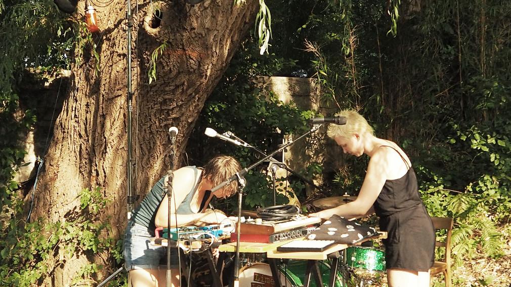Zwei Frauen unter einem Baum bei  einem Mischpult für Tontechnik. Foto: Benjamin Storck.